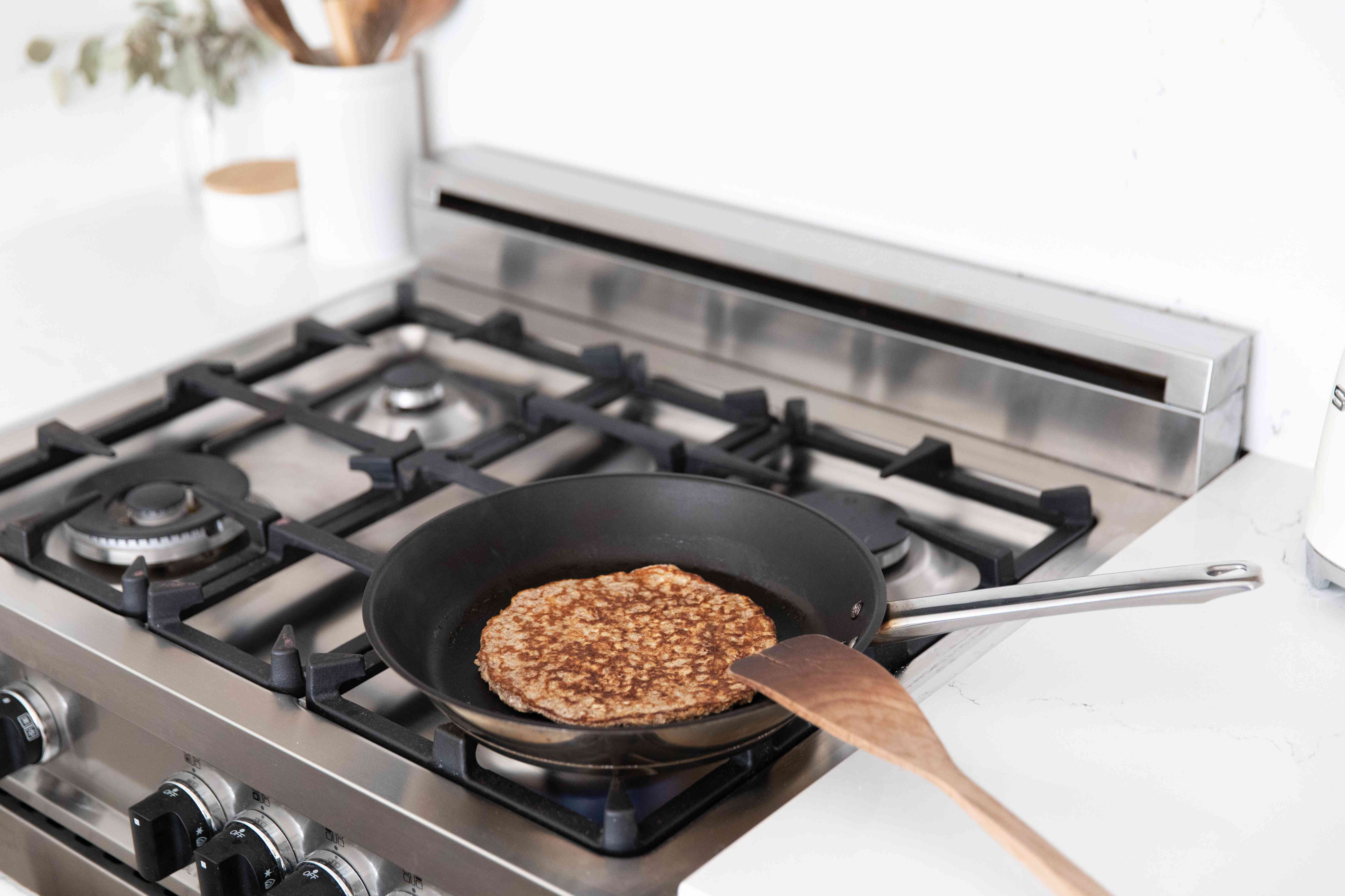 Nonstick pan cooking pancake with wooden spoon