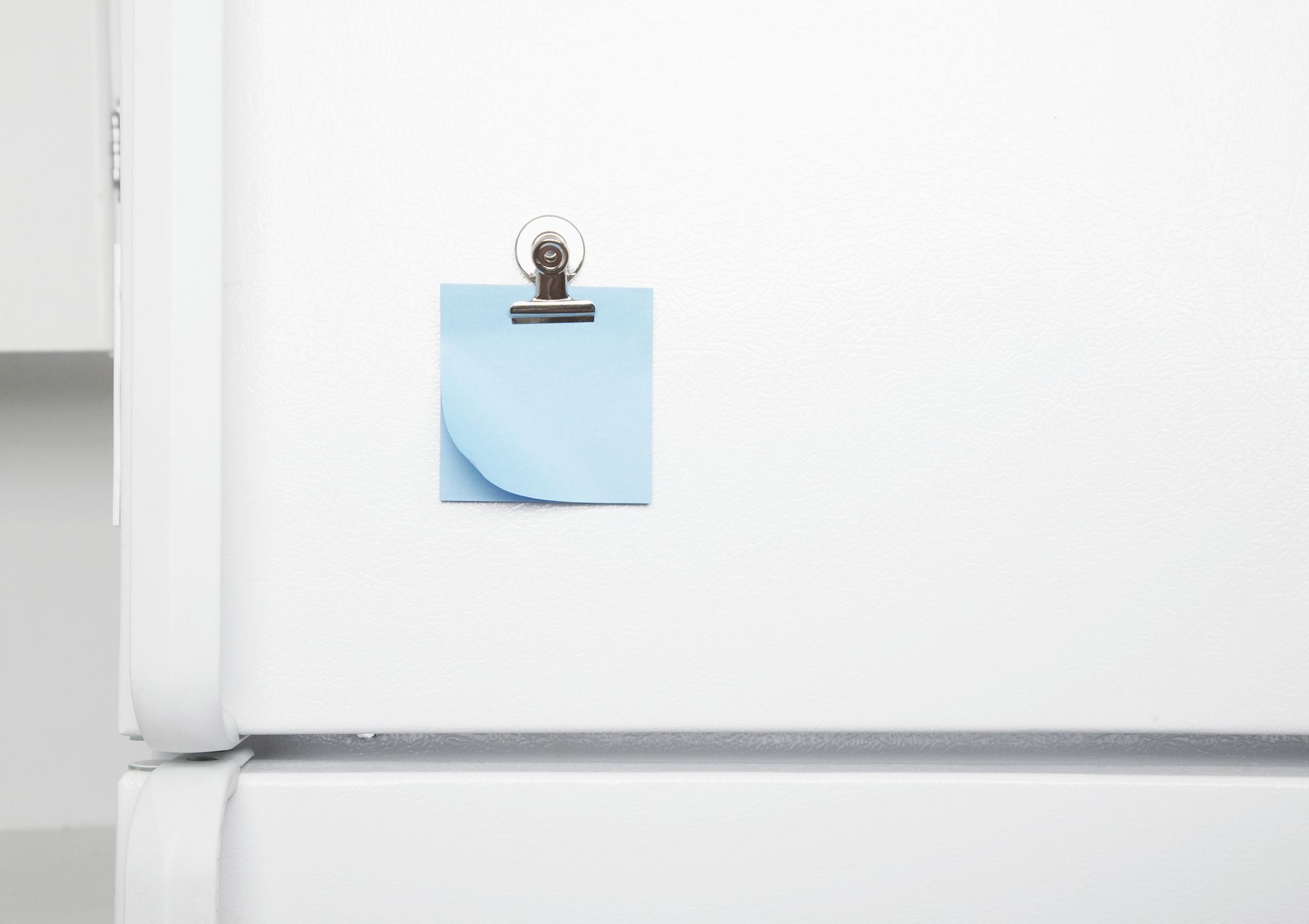 Exterior of refrigerator door with blue sticky note.
