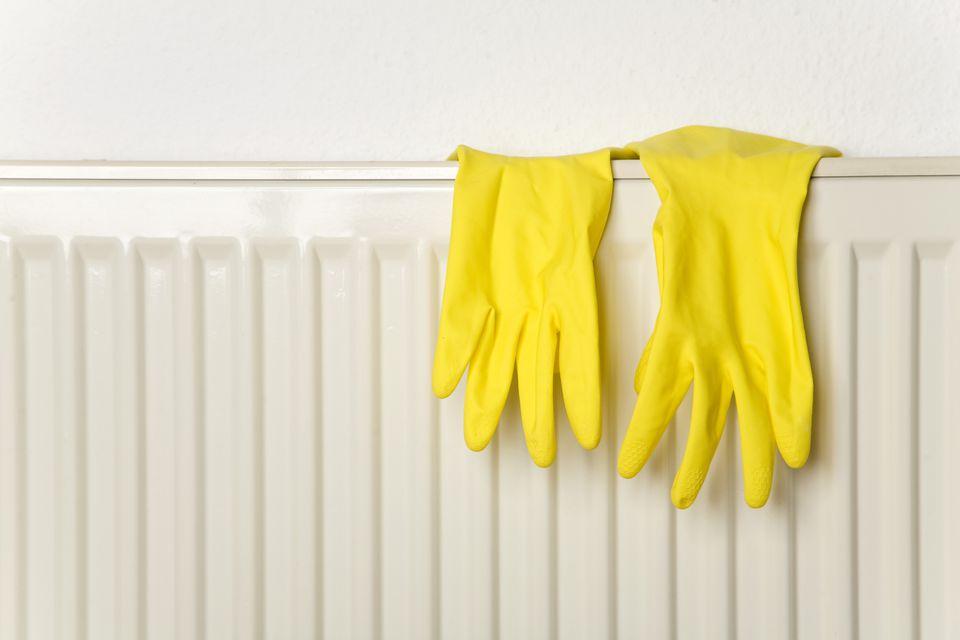 Guantes de goma amarillos sobre el calentador