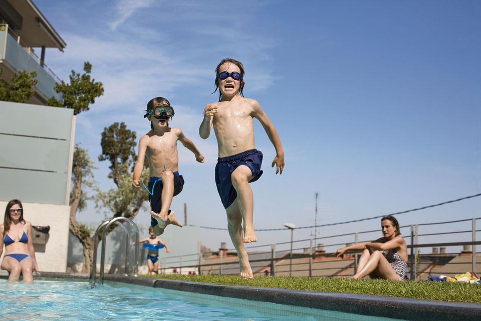 Three boys (3-7) jumping in swimming pool.