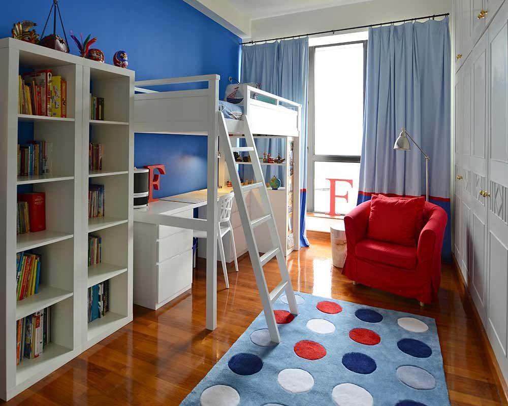 Habitación infantil azul con cama alta y silla roja.