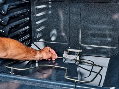 Baking coil in electric oven being replaced by hand