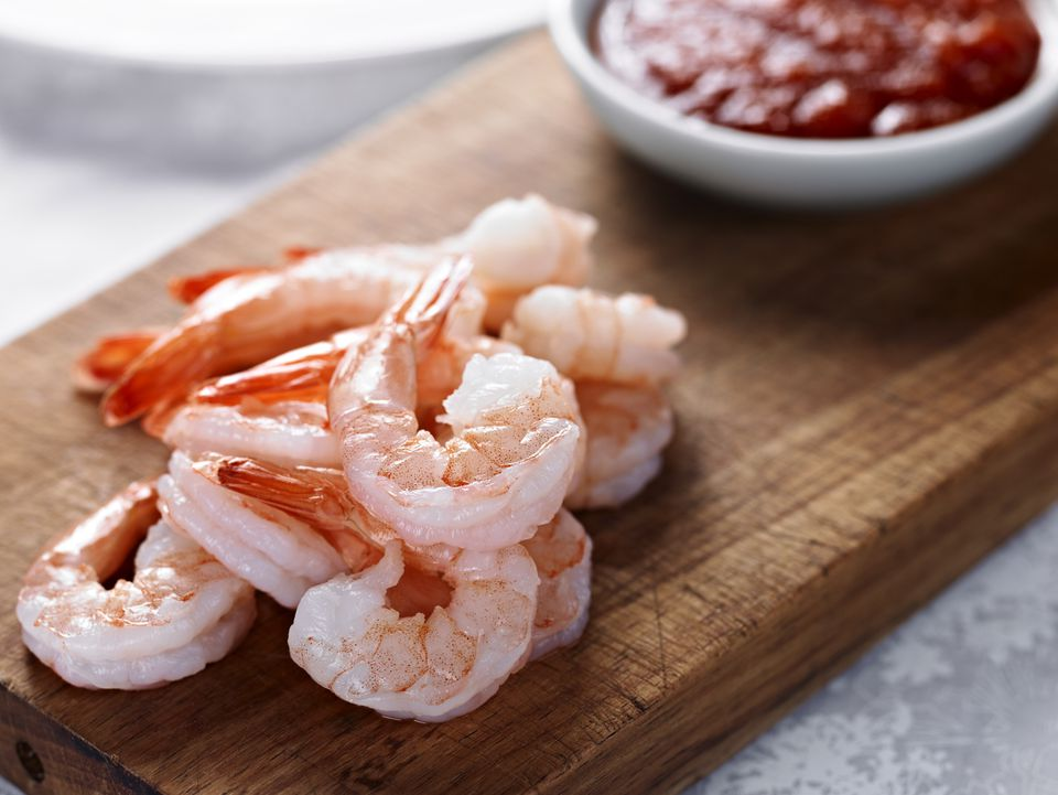 Cooked shrimps on wooden board next to red sauce