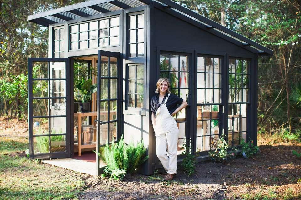 Karissa Cross outside the greenhouse she built