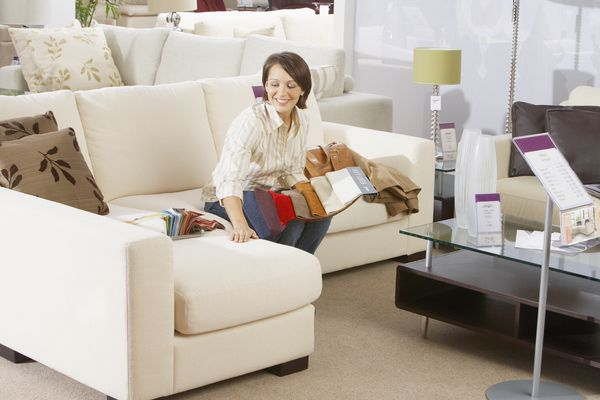 Woman sitting on sofa in furniture store.