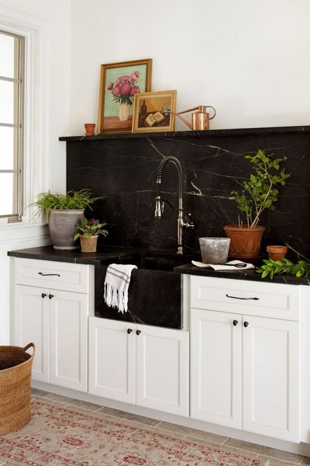 placa para salpicaduras y lavabo de mármol negro sobre gabinetes blancos