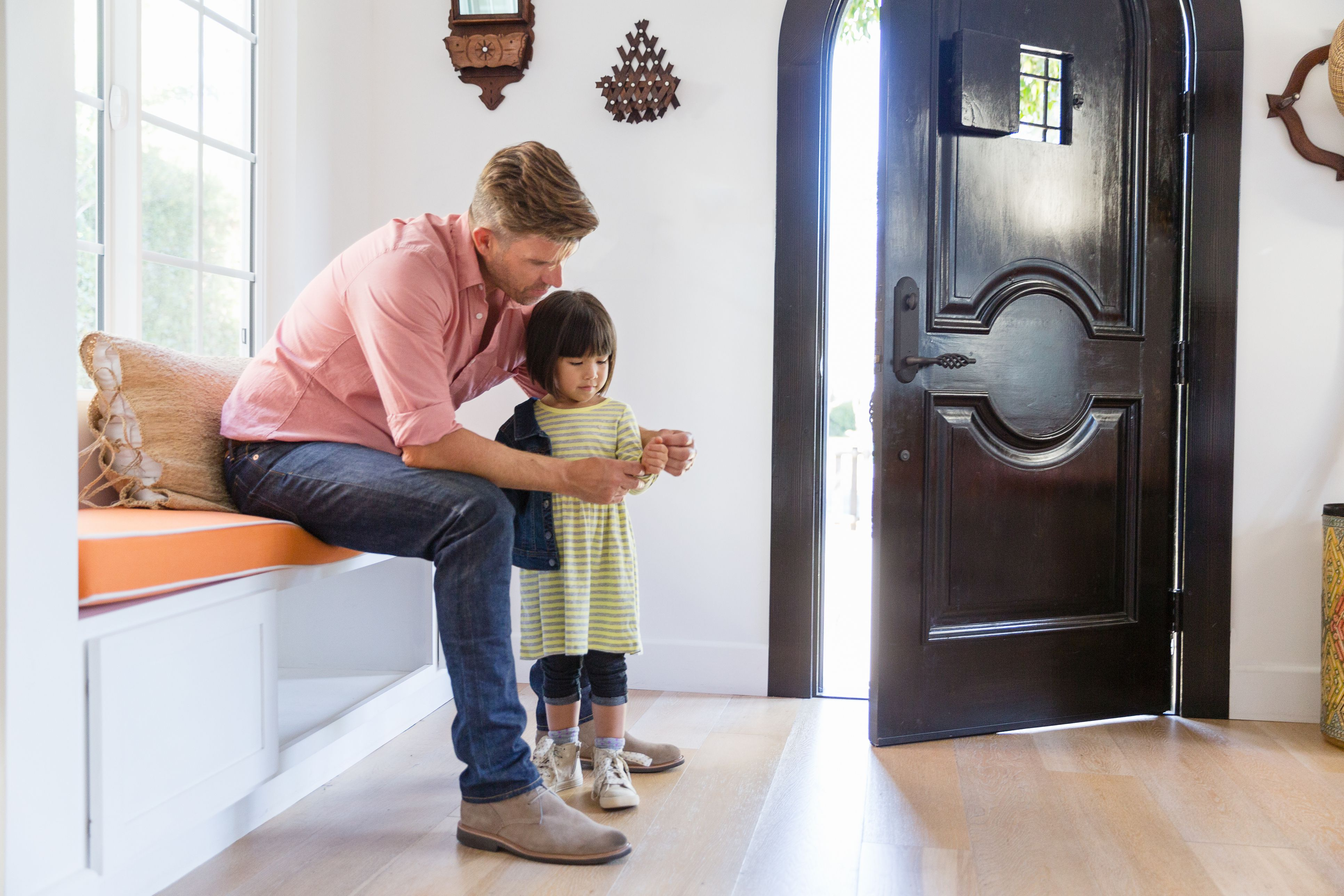 Father putting jacket on toddler daughter in foyer entry