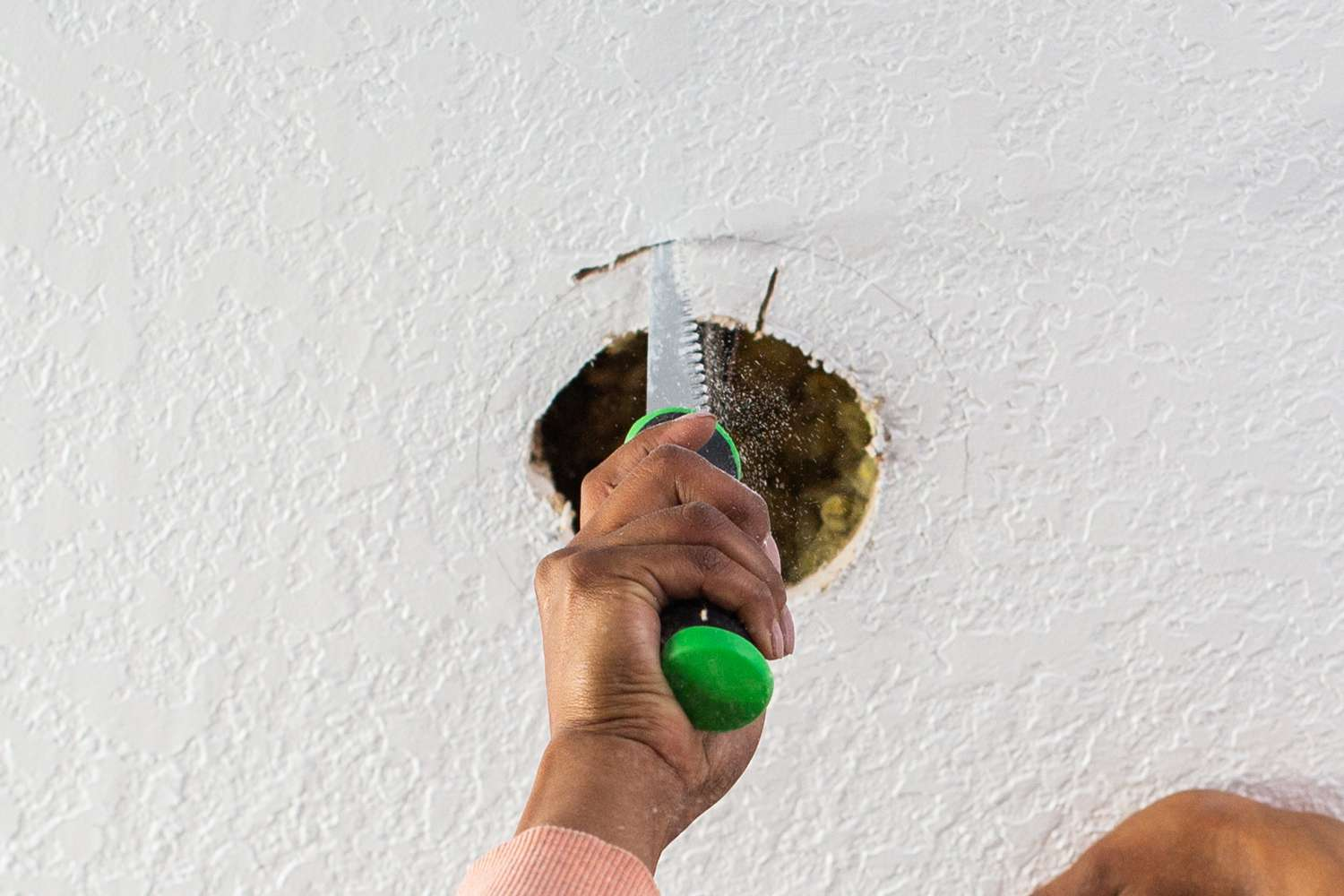 Fixture hole cut out with drywall saw following outline