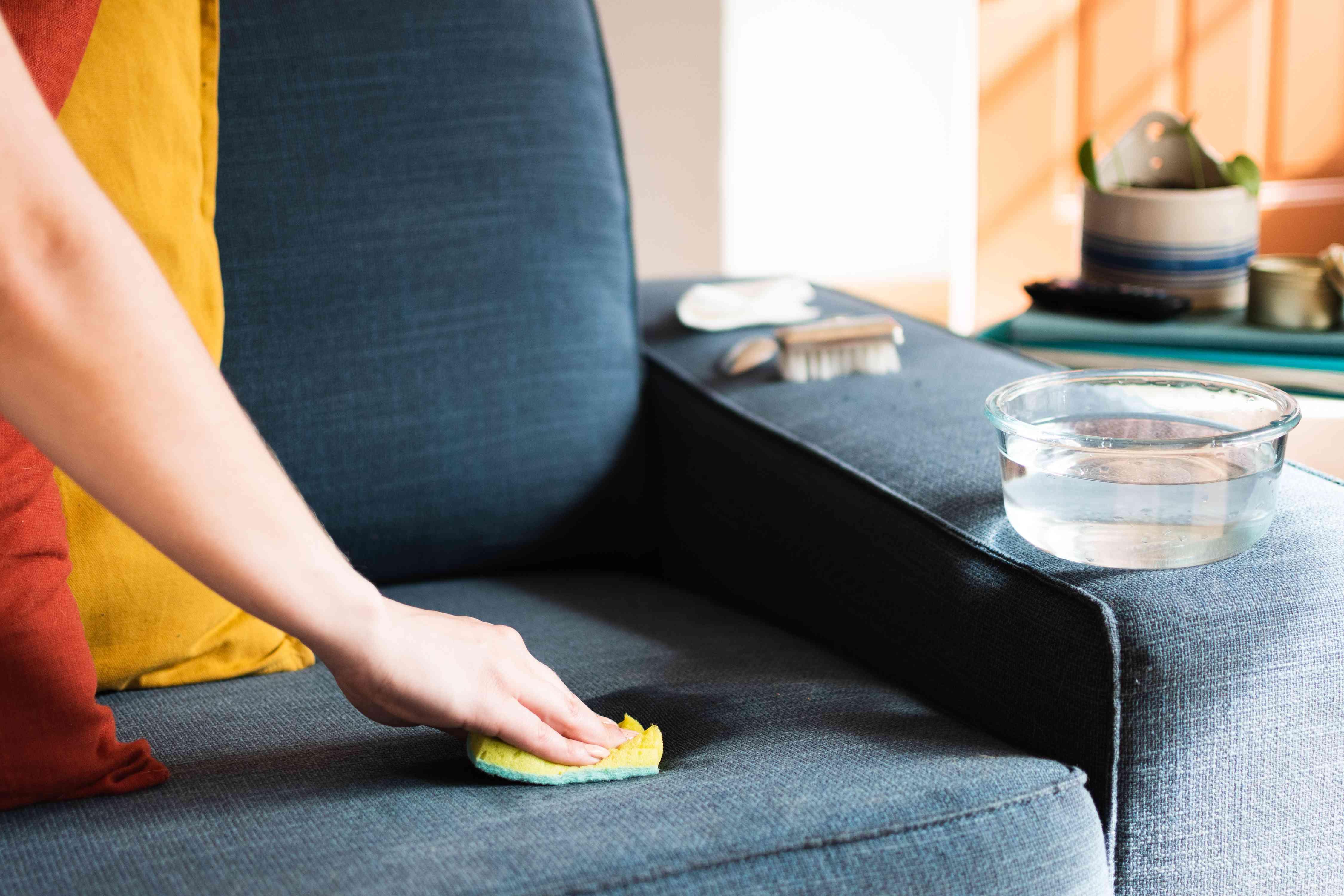 Bọt biển thấm vết bẩn trên ghế dài bọc nệm bằng bát thủy tinh và nước trong trên bệ tỳ tay