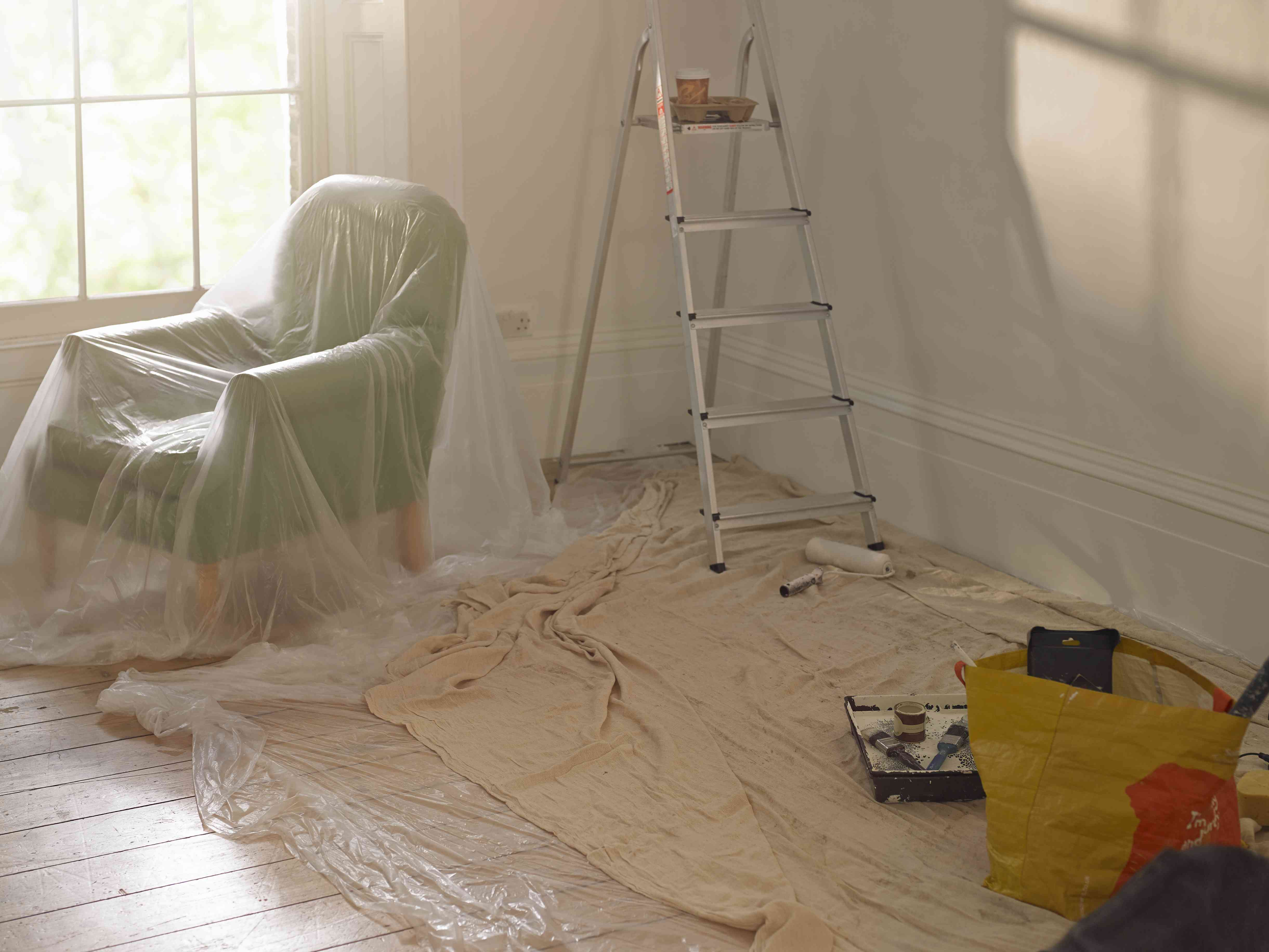 A room with dust sheets, A ladder and paint roller