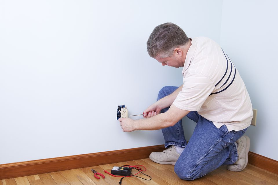An electrician fixing an outlet