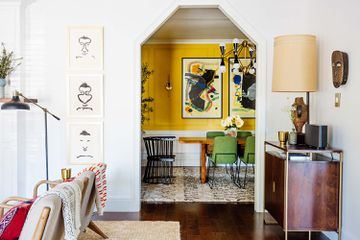 Dabito's living room leads to a yellow dining room with an angular arch