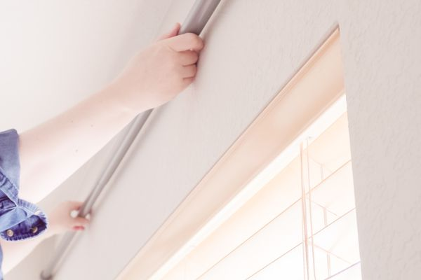 Woman hanging curtains with tension rod