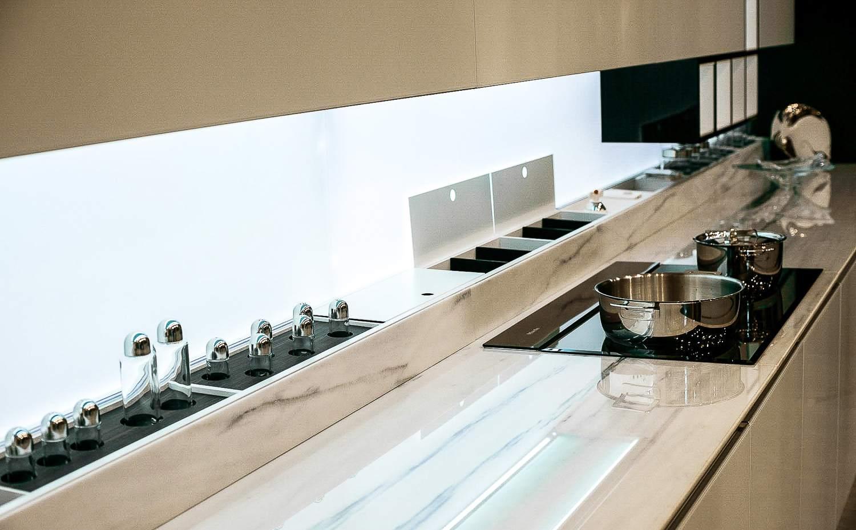 Protector contra salpicaduras iluminado en la moderna cocina detrás de encimeras de mármol