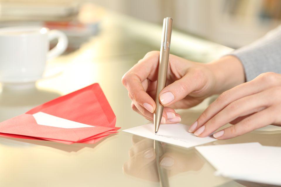 Woman hand writing greeting card at home