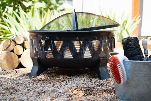 Outdoor fire pit on gravel next to cleaning materials