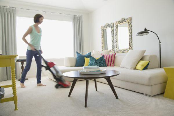 Adult woman vacuuming her contemporary living room.