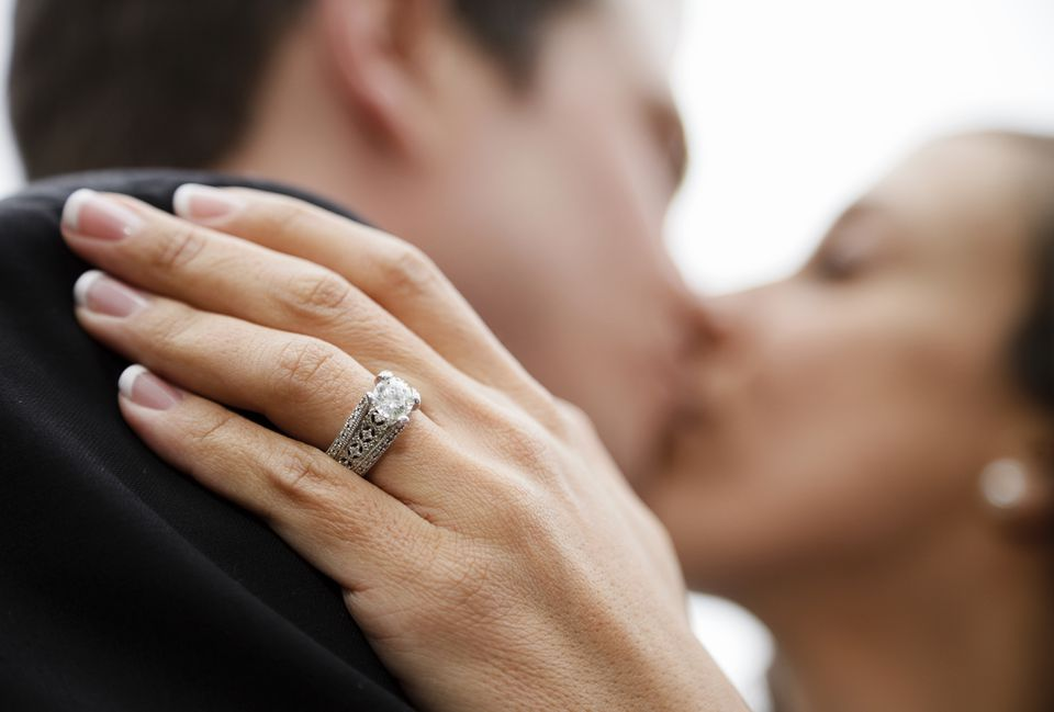 Couple kissing with the camera focusing on the woman's engagement ring placed on his shoulder.