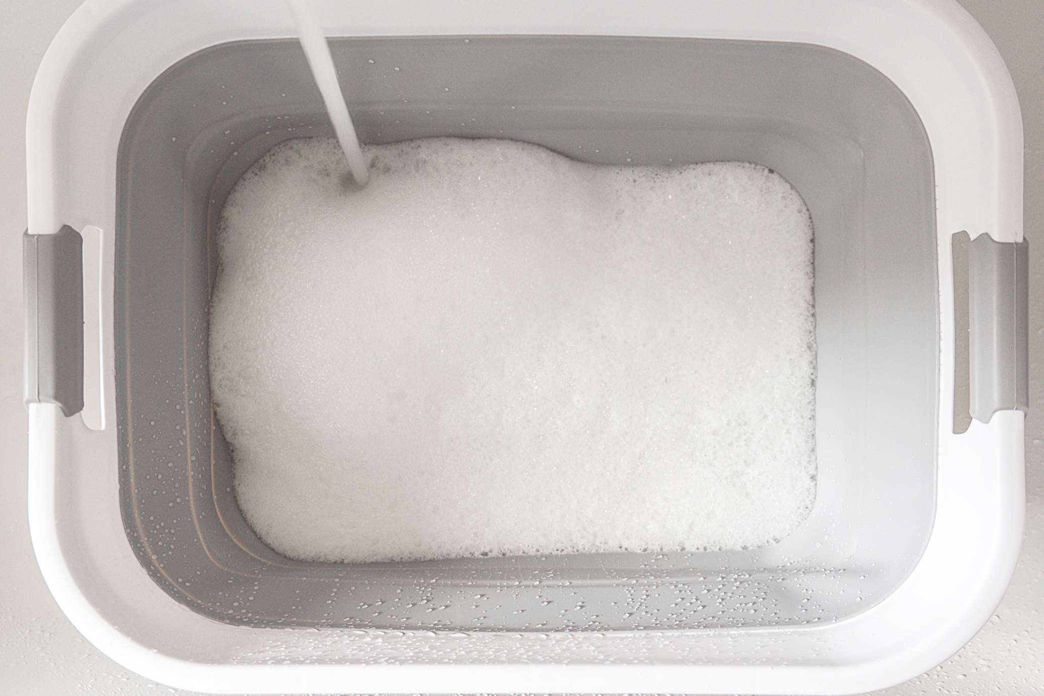 White plastic bin filled with water and high-efficiency gentle detergent