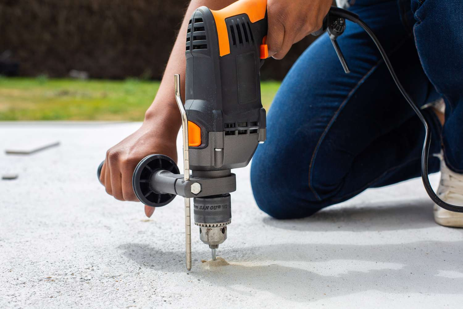 Hammer drill extending drilled hole into concrete