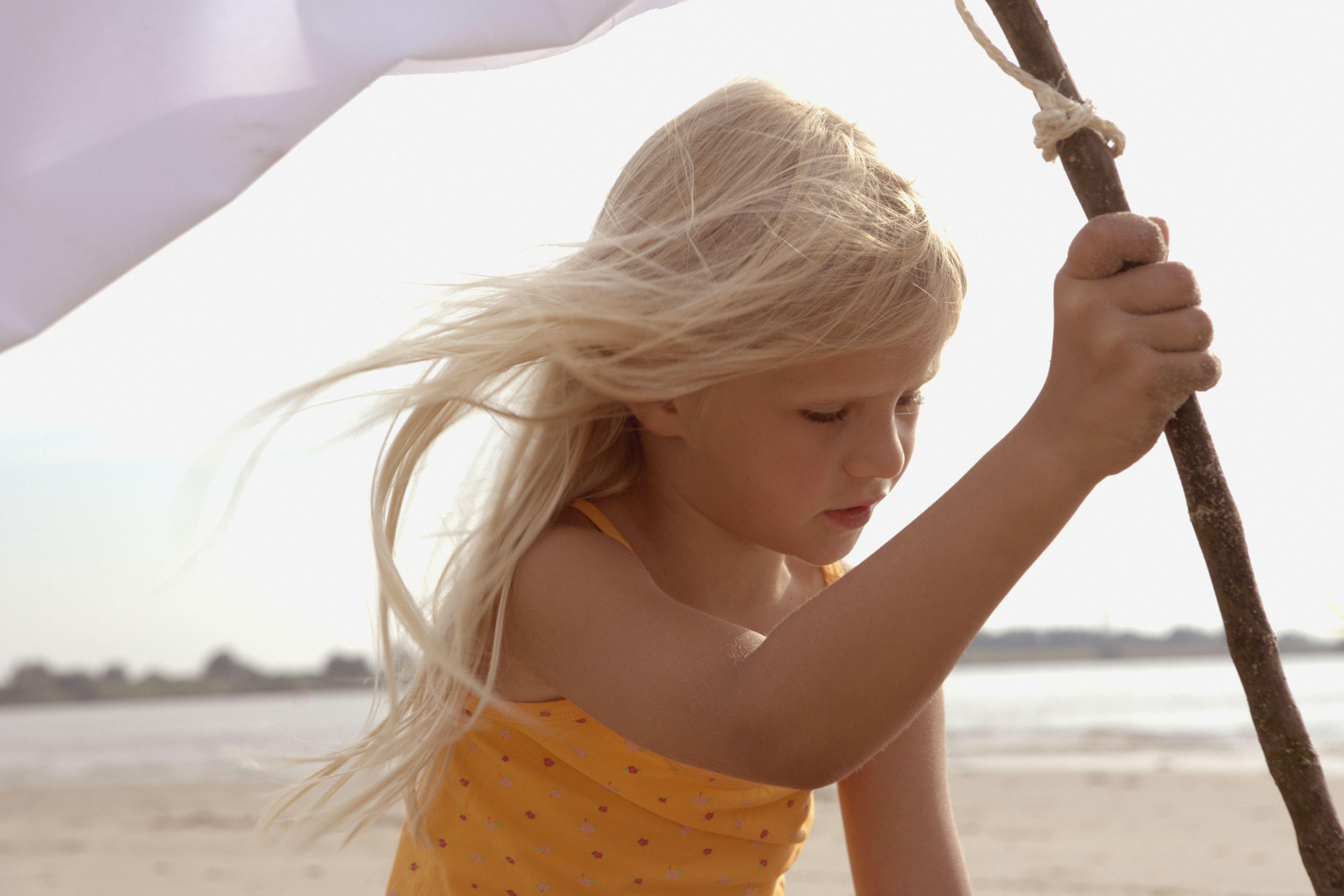 Girl Planting White Flag on Beach