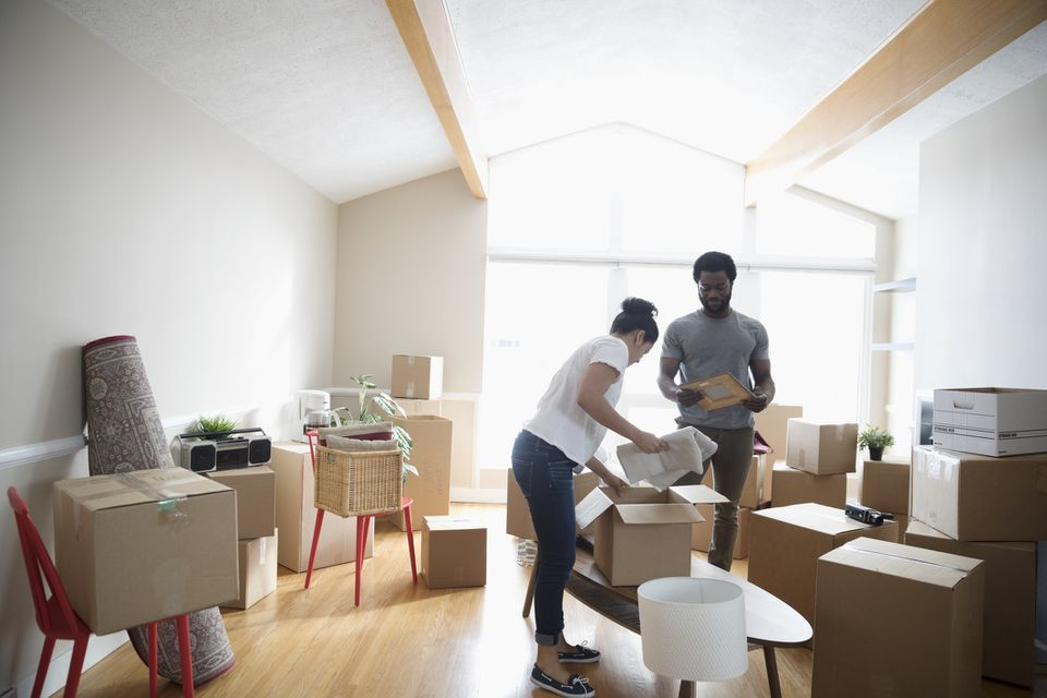 Young couple packing belongings in cardboard boxes, moving house