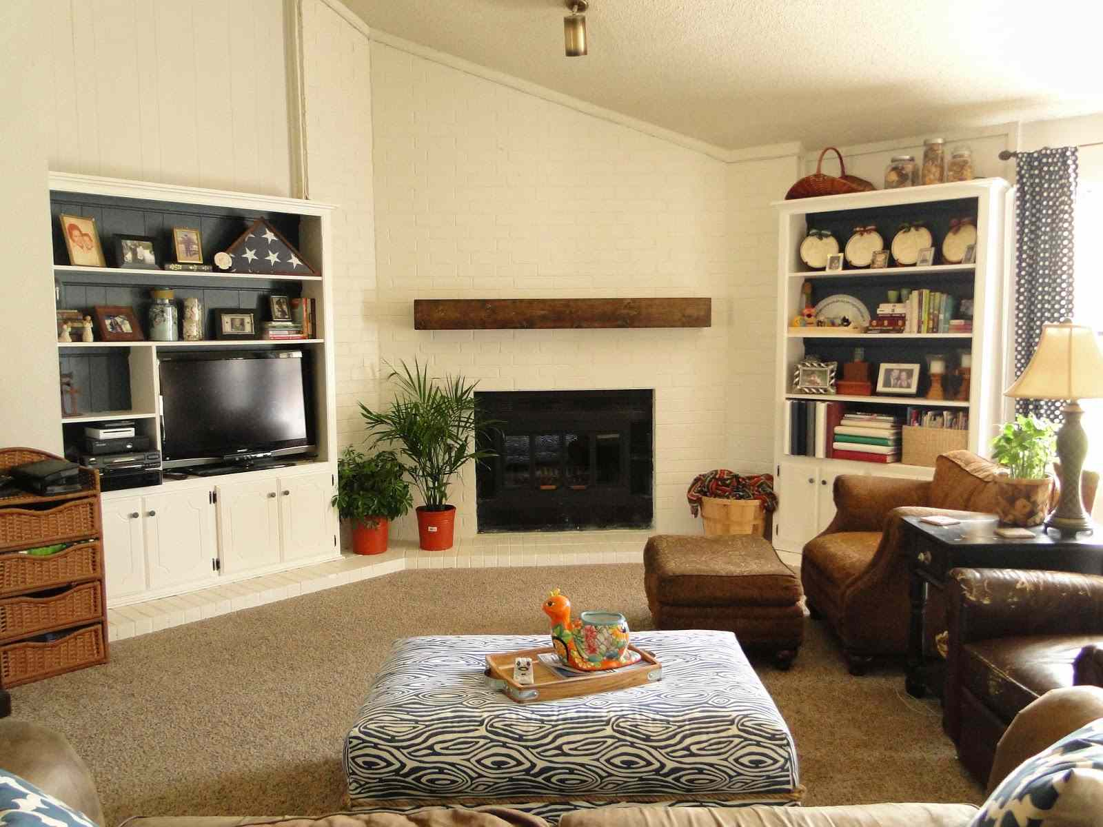 A living room with a fireplace and wooden mantel