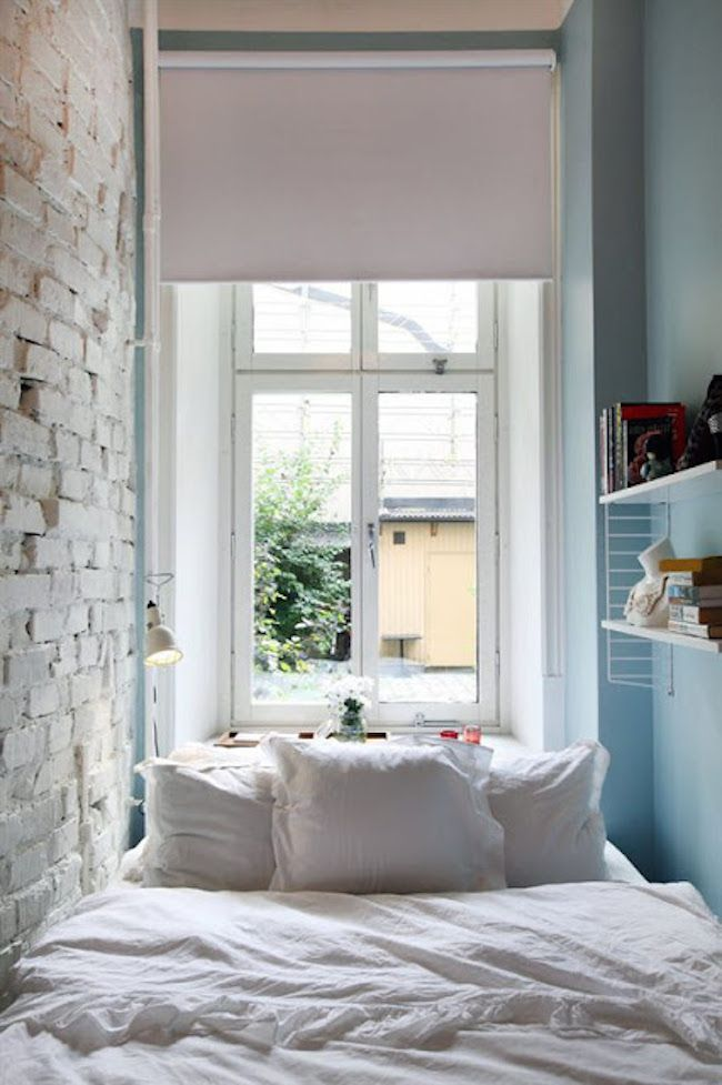 tiny bedroom with a brick wall