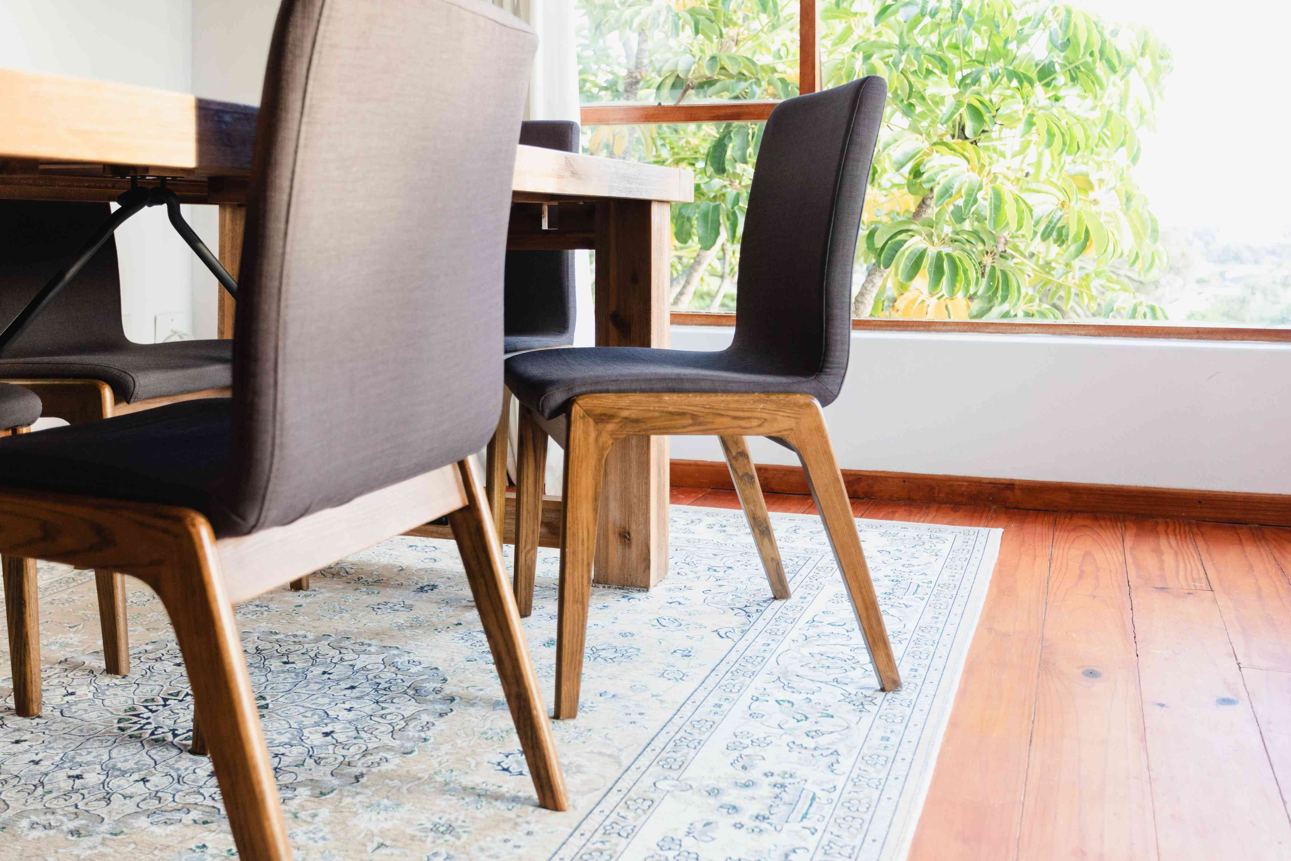 Light colored rug under dining room table with dining chairs pulled out