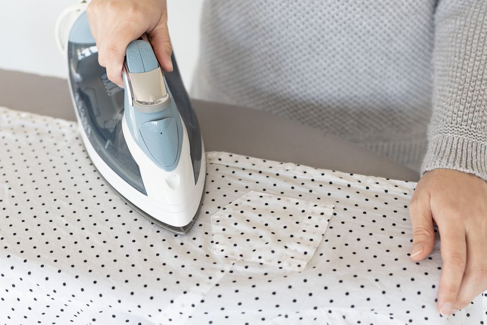 Iron passing over white shirt with black polka dots and starch