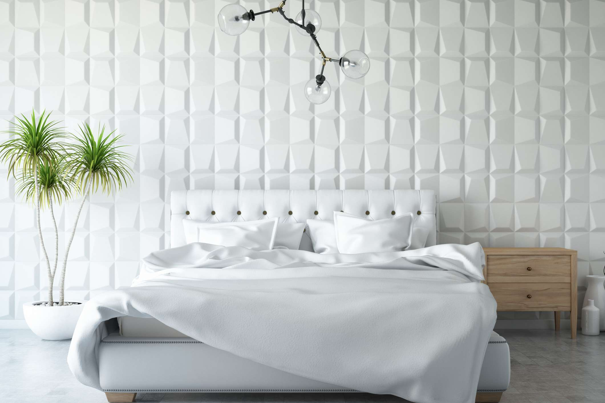 A textured wall and tufted leather headboardadds interest to a white bedroom.
