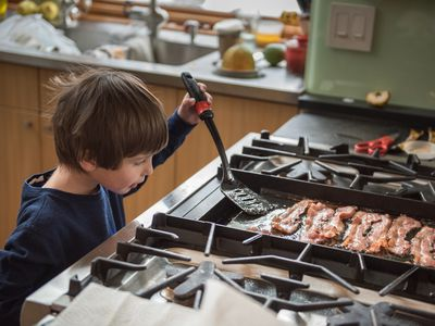 boy cooking bacon on stove top