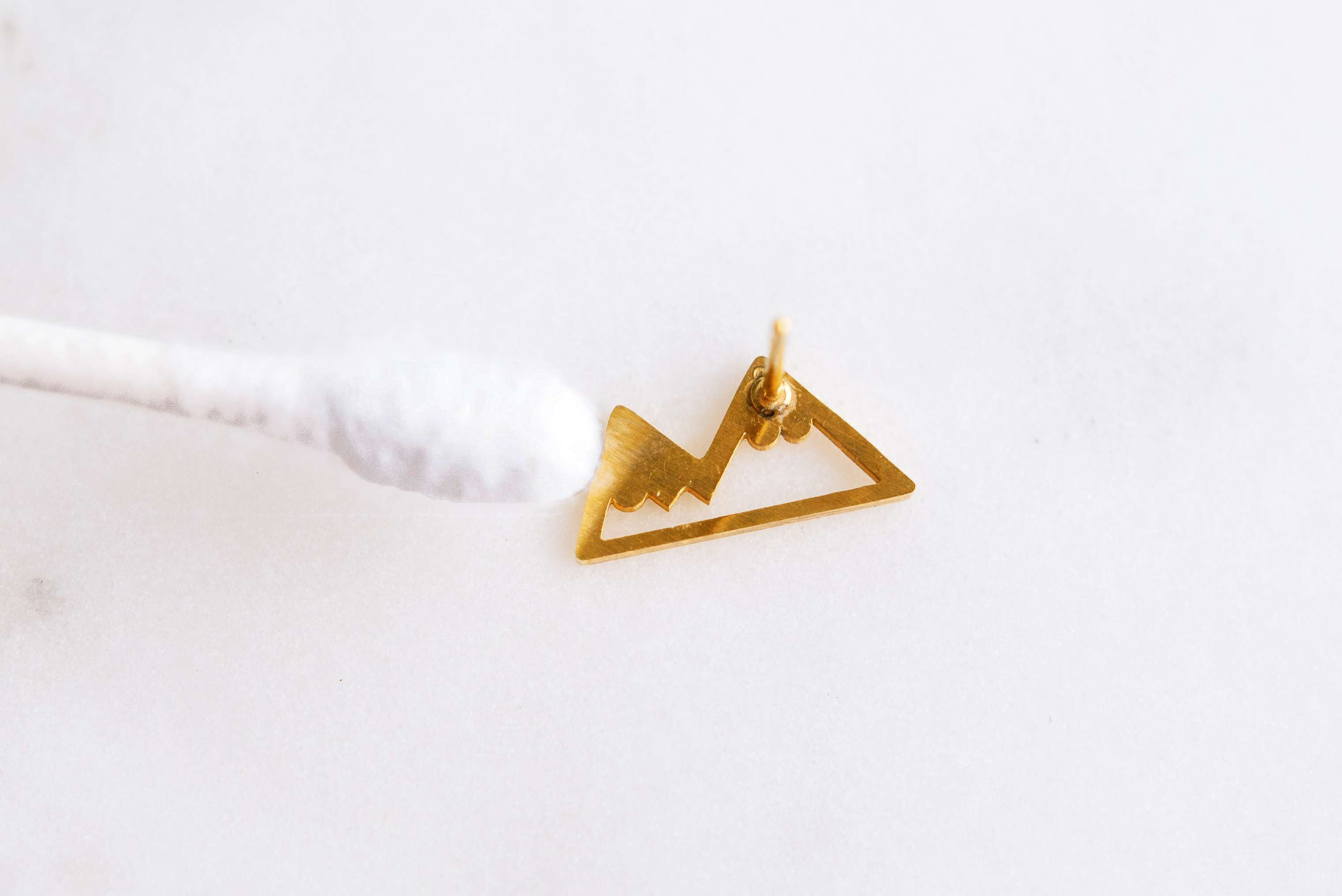 using a cotton swab to clean gold jewelry