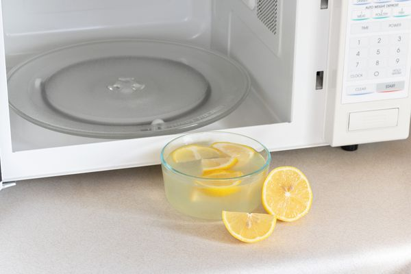 White microwave with door open and sliced lemons inside glass bowl in front