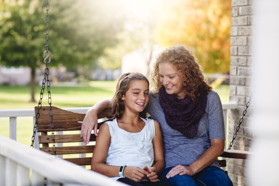 Aunt and niece sitting on porch swing, smiling