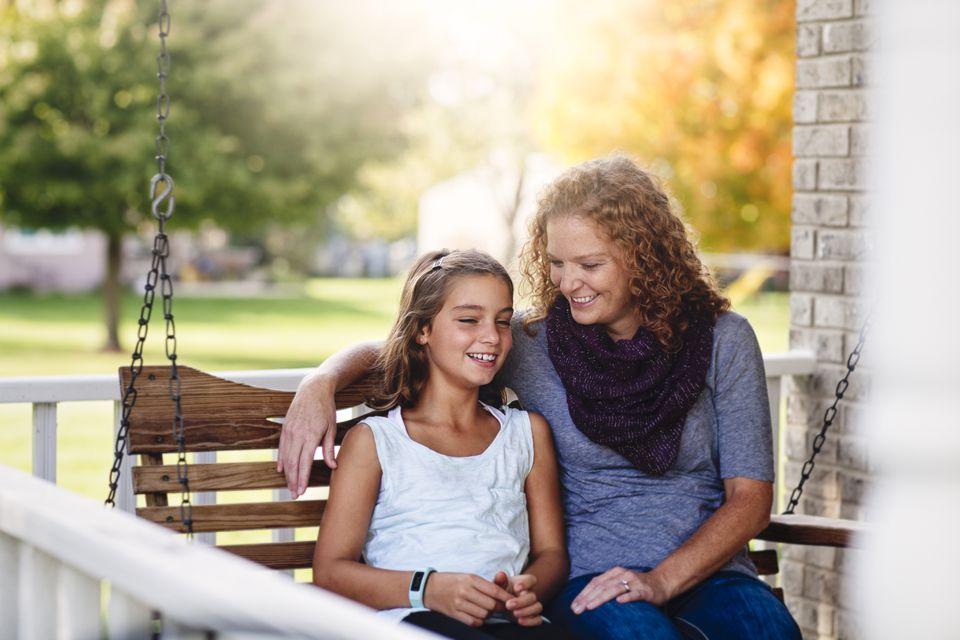 Tía y sobrina sentadas en el columpio del porche, sonriendo