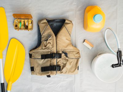 Tan life jacket in middle of yellow oars, bucket of water with hose and a bottle of detergent