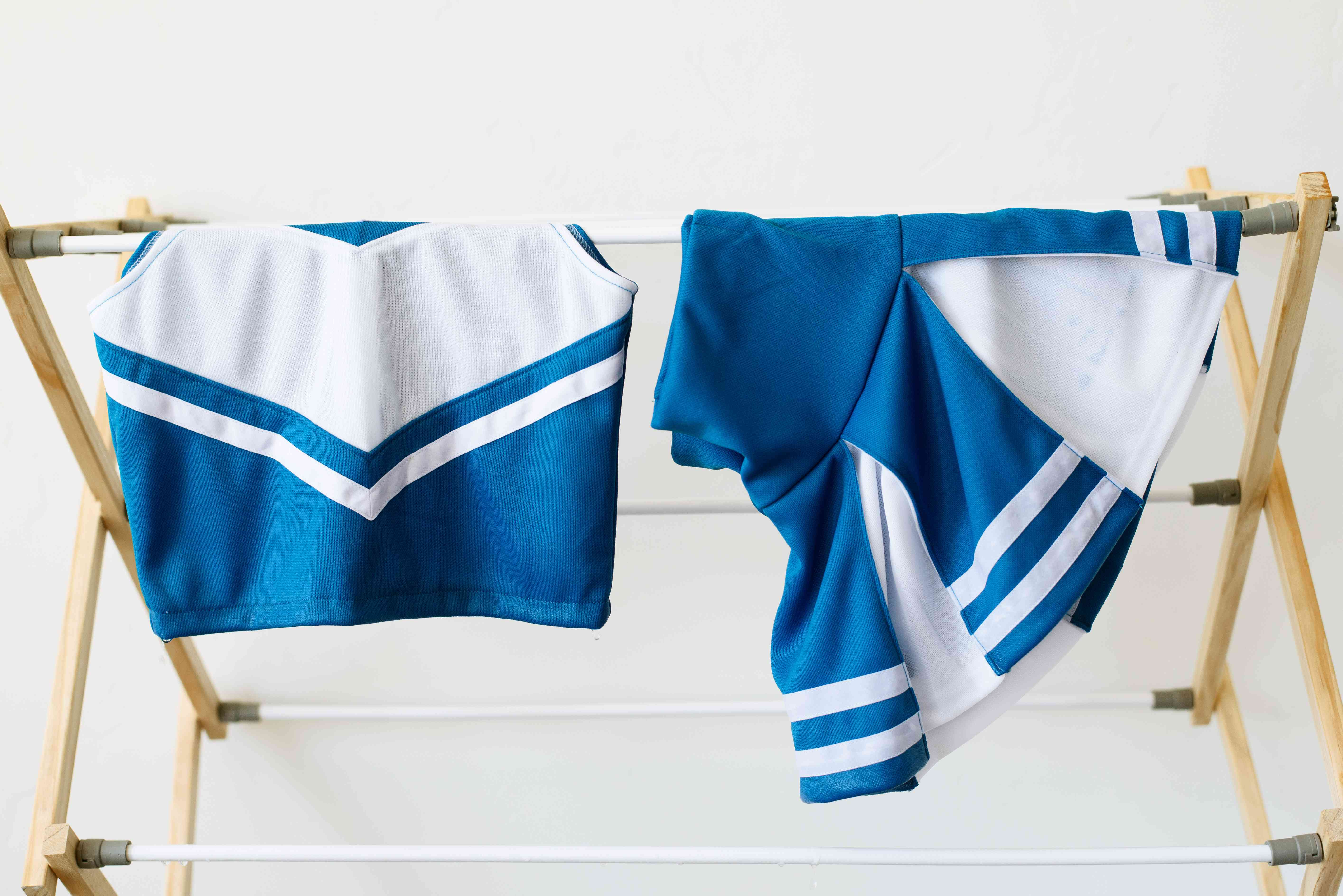 Blue and white cheerleading uniform hanging on drying rack to air dry