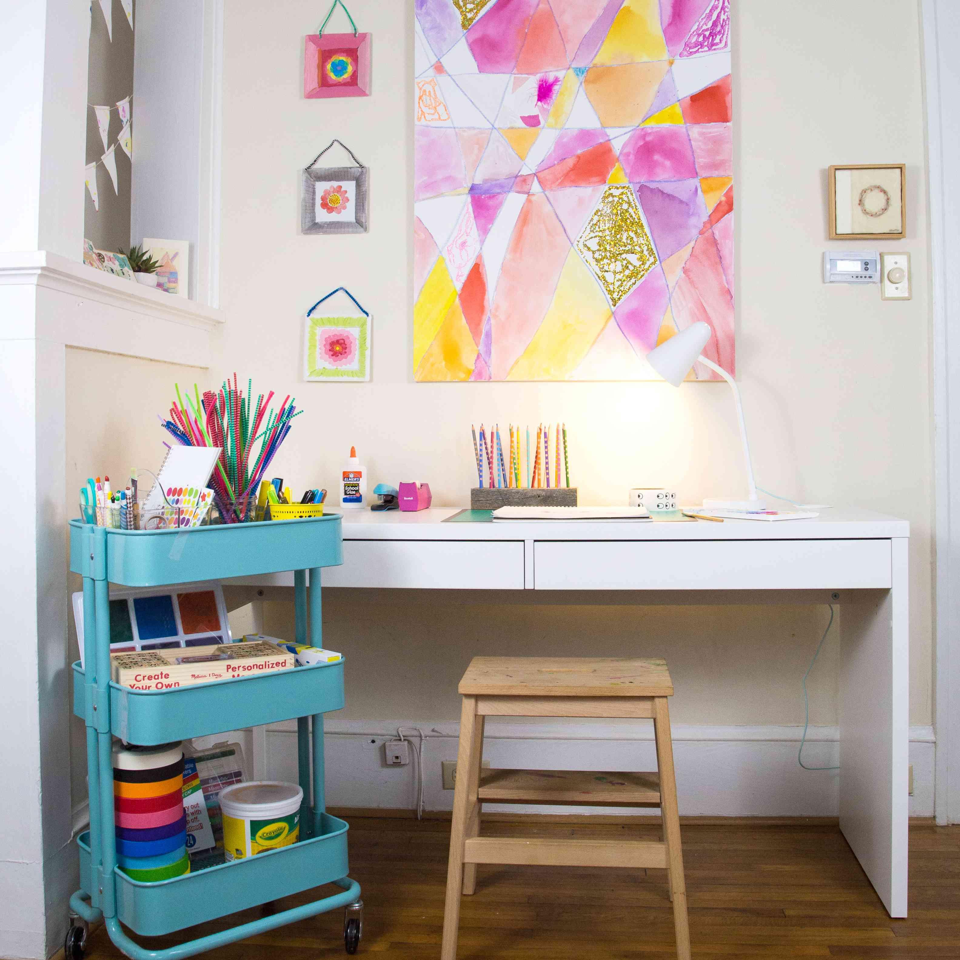 Kids' art corner with hanging displays, storage, and a desk