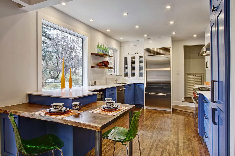 Cocina naranja con isla azul dentro de una cocina blanca