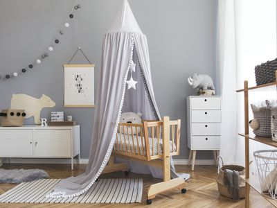 Stylish scandinavian newborn baby room interior with mock up poster , white furnitures, natural toys, hanging grey canopy with stars and teddy bears. Minimalistic and cozy interior of child room.