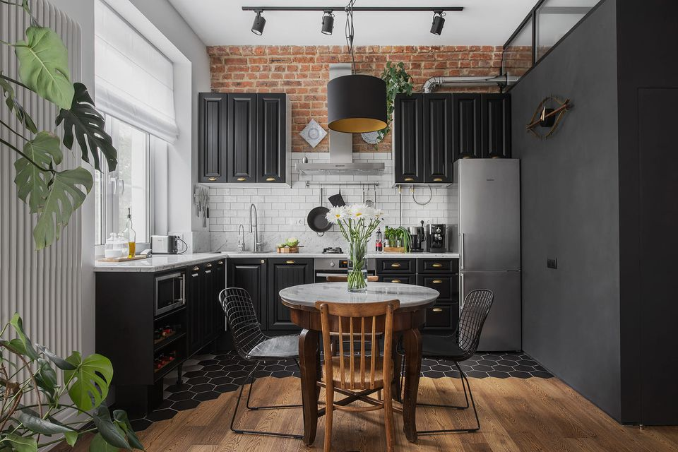 Black kitchen cabinets with brick and white subway tile behind them