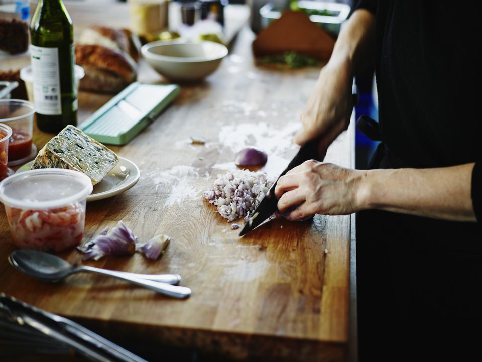 Woman chopping an onion on a wooden kitchen counter