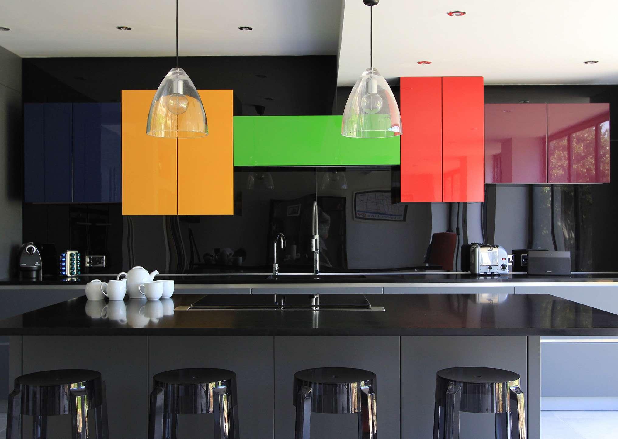 Encimeras de cuarzo negro brillante con gabinetes de color amarillo, verde, azul, rojo y morado