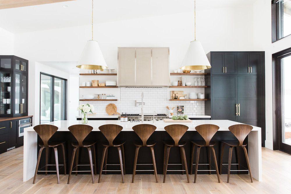 cocina grande con gabinetes negros y barra de madera sillas de taburete