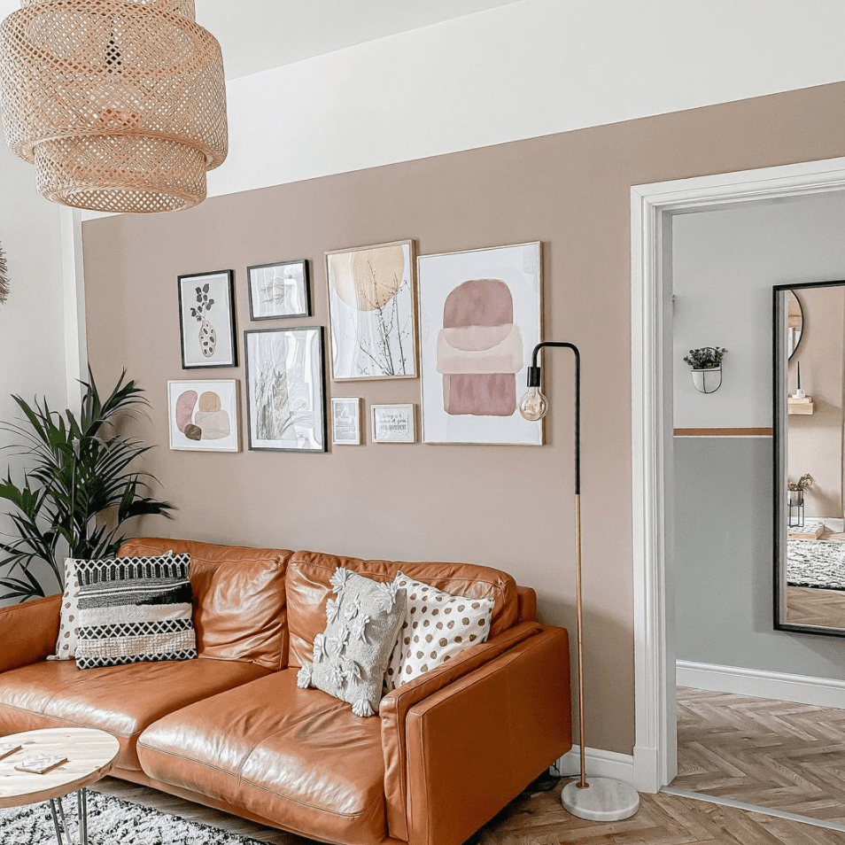A classic gallery wall over a leather couch.