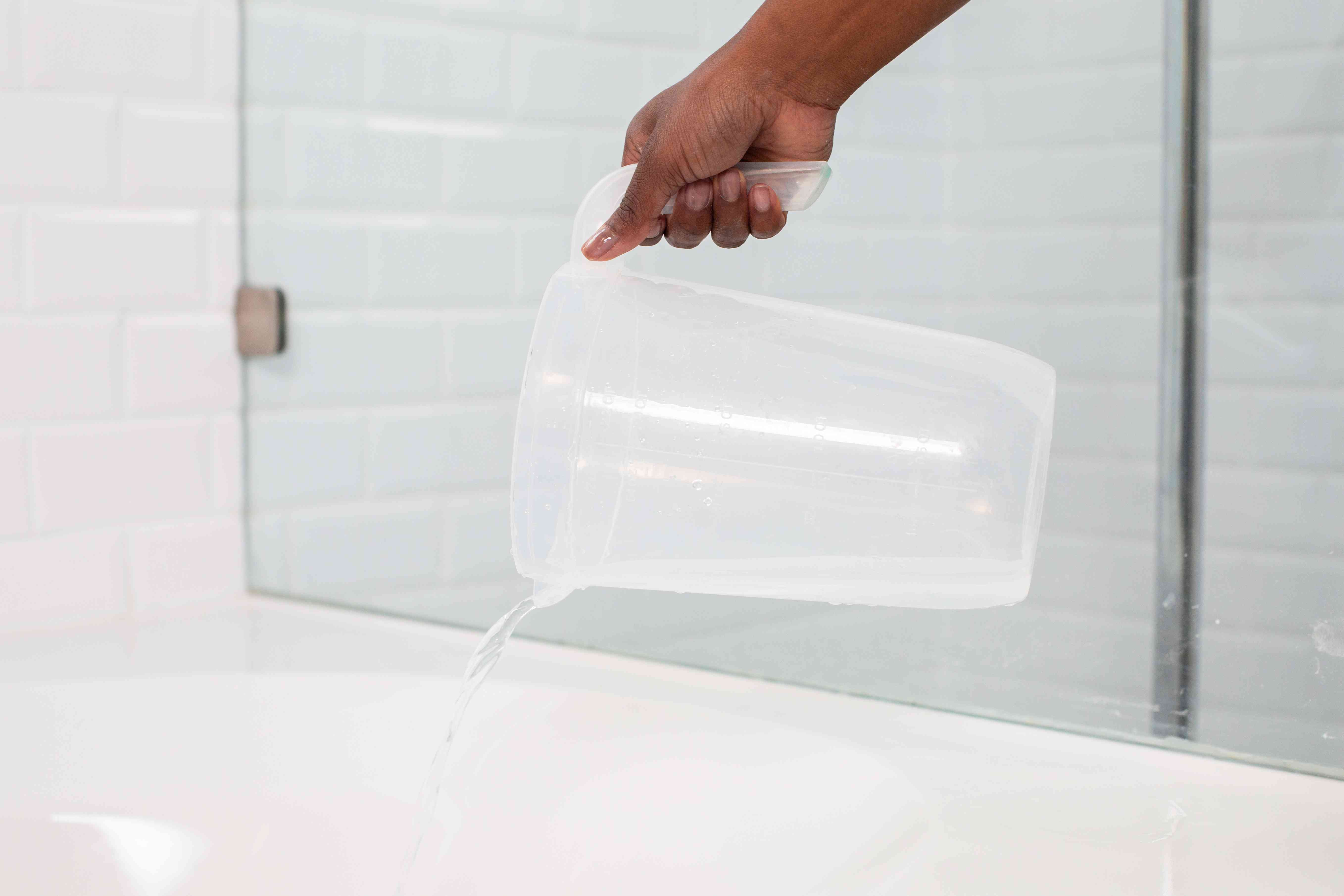 Bathtub rinsed with plastic pitcher pouring water