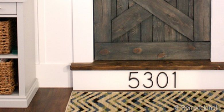 House numbers on a stair riser in front of the door.