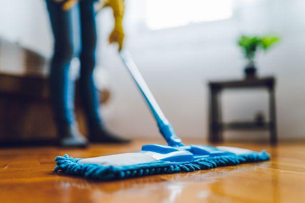 Someone using dust mop on hardwood floor