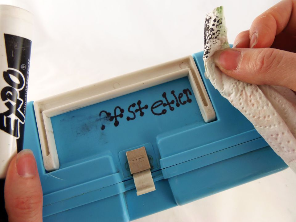 Person cleaning permanent marker off plastic lunchbox